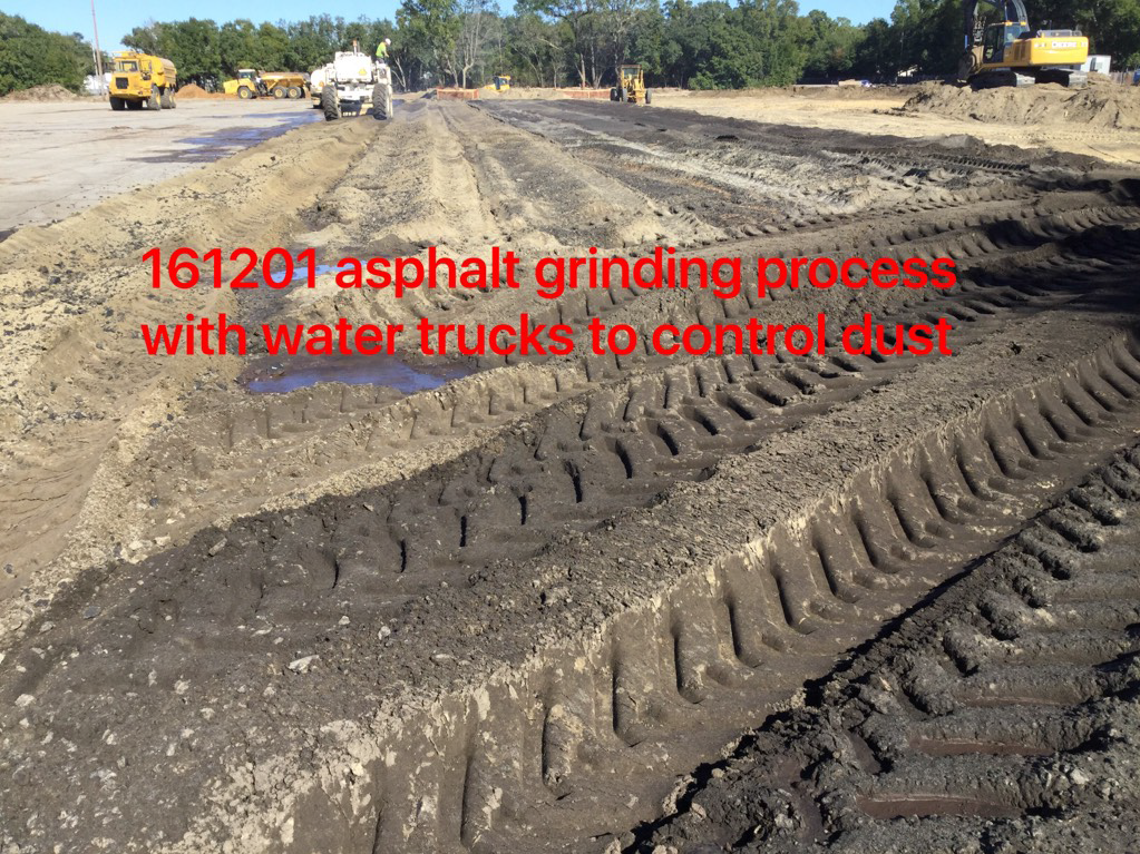 Asphalt grinding process with water trucks to control dust.