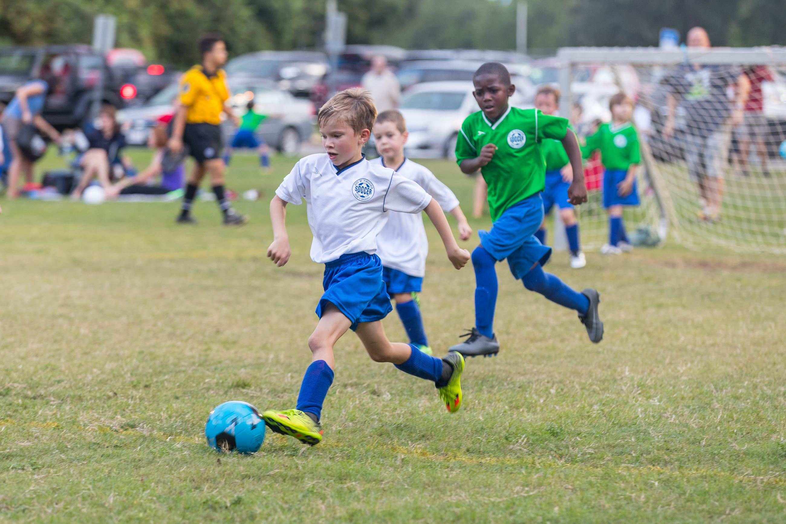 Young boy in blue and white uniform kicking soccer ball